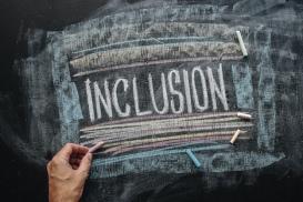 Teacher writing word Inclusion on school blackboard, inclusive education